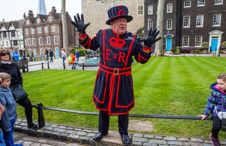 LONDON, UK - APRIL 10TH 2016: A Yeomen Warder talking to visitors during a tour of the historic Tower of London, on 10th April 2016.