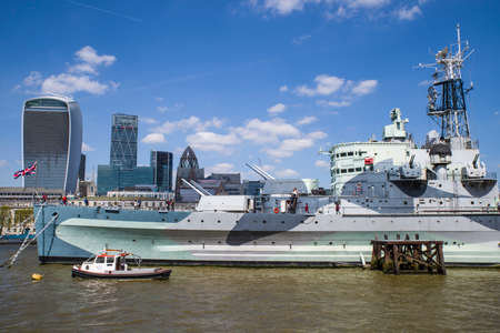 hms: A view of the HMS Belfast on the River Thames in London.  The skyscrapers of the City of London can be seen in the background.