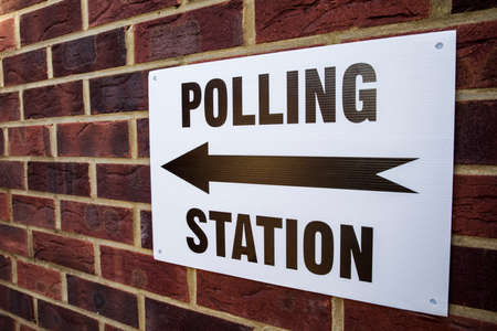 encuestando: Una se�al fuera un centro de votaci�n el d�a de elecciones en el Reino Unido.