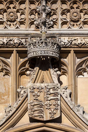 A close-up of the Royal Crown and Coat of Arms on the gatehouse of King's College in Cambridge, UK.