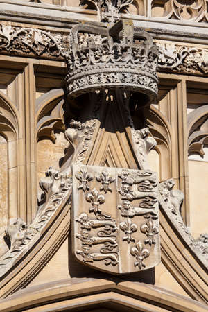 crown spire: A close-up of the Royal Crown and Coat of Arms on the gatehouse of King's College in Cambridge, UK.