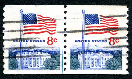 postmarked: UNITED STATES OF AMERICA - CIRCA 1971: A used postage stamp from the USA depicting an illustration of the White House and the American flag, circa 1971.