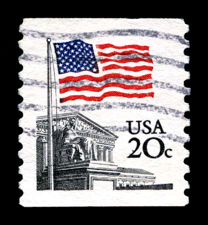 postmarked: UNITED STATES OF AMERICA - CIRCA 1988: A used postage stamp from the United States of America, portraying and illustration of the American Flag and the Supreme Court, circa 1988.