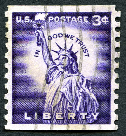 in god we trust: UNITED STATES OF AMERICA - CIRCA 1954: A used US postage stamp depicting an illustration of the Statue of Liberty and the quote In God We Trust, circa 1954.
