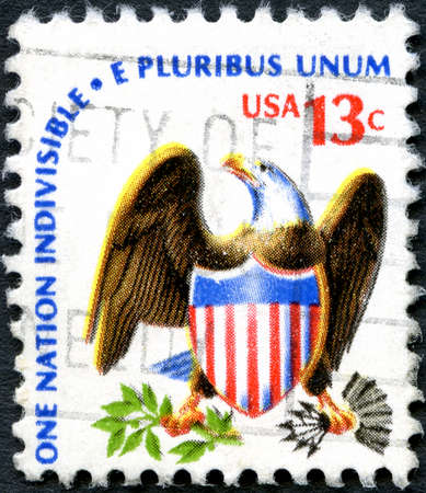 unum: UNITED STATES OF AMERICA - CIRCA 1975: A used postage stamp from the USA depicting the American Eagle and flag and a line from the pledge of Allegiance, circa 1975.