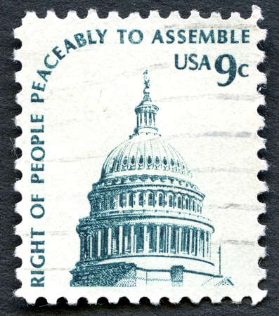 peaceably: UNITED STATES OF AMERICA - CIRCA 1975: A used postage stamp from the USA depicting an illustration of the Capitol building in Washington and the phrase 'Right of People Peaceably to Assemble, circa 1975. Editorial