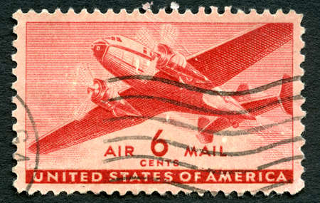 air plane: UNITED STATES OF AMERICA - CIRCA 1943: A used US Air Mail postage stamp depicting an illustration of a vintage transport plane, circa 1943.