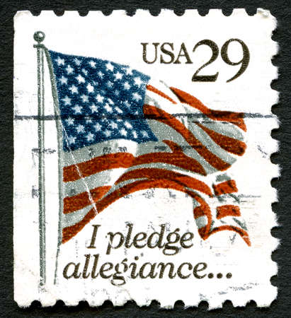 pledge of allegiance: UNITED STATES OF AMERICA - CIRCA 1992: A used postage stamp from the USA, depicting an ilustration of the US Flag and the first line of the Pledge of Allegiance, circa 1992.