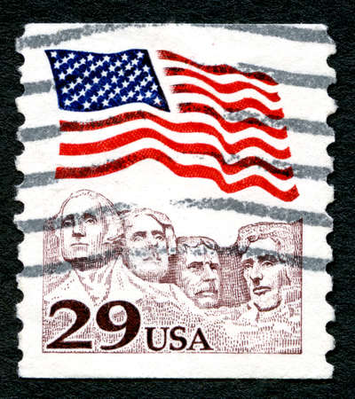 mount rushmore: UNITED STATES OF AMERICA - CIRCA 1991: A used postage stamp from the USA, depicting an illustration of the American flag and historic landmark Mount Rushmore, circa 1991. Editorial