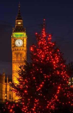 Une vue d'un bel arbre de Noël illuminé avec la tour Elizabeth des Chambres du Parlement en arrière-plan, Londres.
