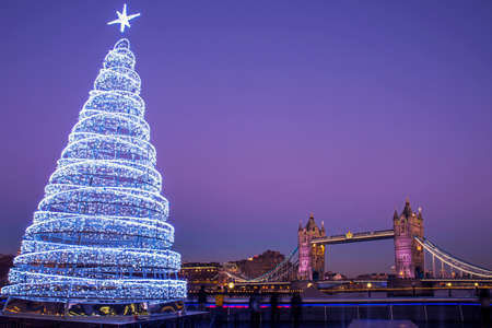 A view of the magnificent Tower Bridge with an illuminated Christmas Tree in London.
