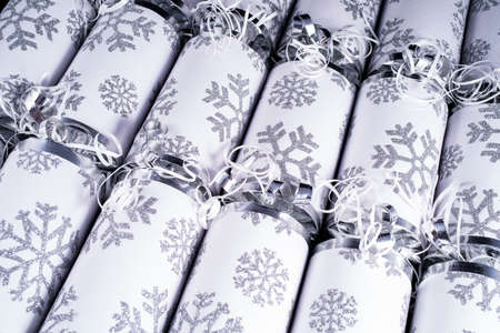central chamber: A studio shot of a set of Christmas Crackers or otherwise known as Bon Bons.  A cracker consists of a cardboard tube wrapped in a decorated twist of paper with a gift in the central chamber. Stock Photo