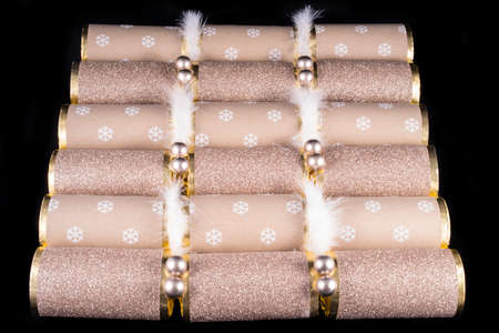 central chamber: A studio shot of a set of Christmas Crackera or otherwise known as Bon Bons.  A cracker consists of a cardboard tube wrapped in a decorated twist of paper with a gift in the central chamber. Stock Photo