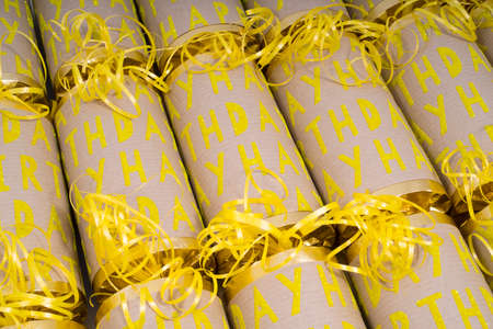 central chamber: A studio shot of Happy Birthday Crackers or otherwise known as Bon Bons.  A cracker consists of a cardboard tube wrapped in a decorated twist of paper with a gift in the central chamber. Stock Photo