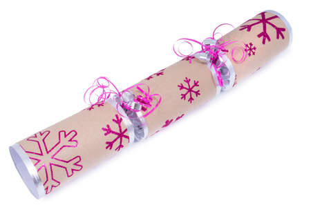 central chamber: A studio shot of a Christmas Cracker or otherwise known as a Bon Bon.  A cracker consists of a cardboard tube wrapped in a brightly decorated twist of paper with a gift in the central chamber.