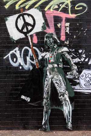 unify: LONDON, UK - JANUARY 13TH 2016: Urban Street Art by UNIFY portraying an image of Darth Vader holding a Ban the Bomb sign, in East London on 13th January 2016.