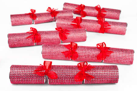 A studio shot of a set of Crackers or otherwise known as Bon Bons.  A traditional cracker consists of a cardboard tube wrapped in a brightly decorated twist of paper with a gift in the central chamber.