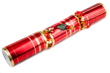 central chamber: A studio shot of a Christmas Cracker or otherwise known as a Bon Bon.  A traditional cracker consists of a cardboard tube wrapped in a brightly decorated twist of paper with a gift in the central chamber. Stock Photo