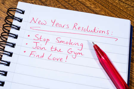 new years resolutions: A list of New Years Resolutions written on a notepad. Stock Photo