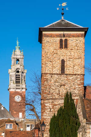 A view of the old Saxon tower of the Holy Trinity church with the Victorian tower of Colchester Town Hall in the background, in the historic town of Colchester, Essex. Stock Photo