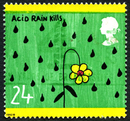 kwaśne deszcze: UNITED KINGDOM - CIRCA 1992: A used postage stamp from the UK, depicting an illustration of a flower dying in the rain promoting the message that Acid Rain Kills, circa 1992.