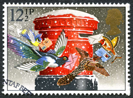 GREAT BRITAIN - CIRCA 1983: A used postage stamp from the UK, depicting a festive illustration of birds posting Christmas cards and letters, circa 1983. Editorial