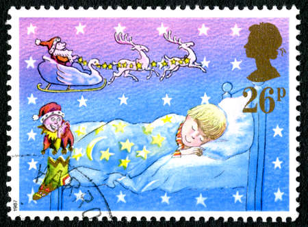 GREAT BRITAIN - CIRCA 1987: A used postage stamp from the UK, depicting a festive illustration of a young boy dreaming about Santa Claus and Christmas gifts, circa 1987.