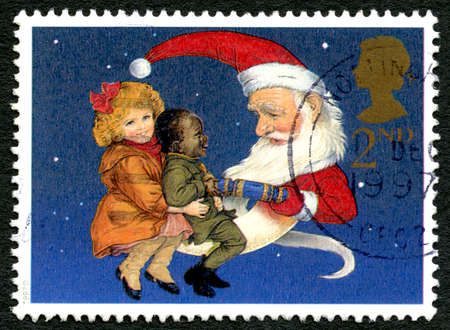 GREAT BRITAIN - CIRCA 1997: A used postage stamp from the UK, depicting an illustration of two children sitting on the lap of Father Christmas, circa 1997.