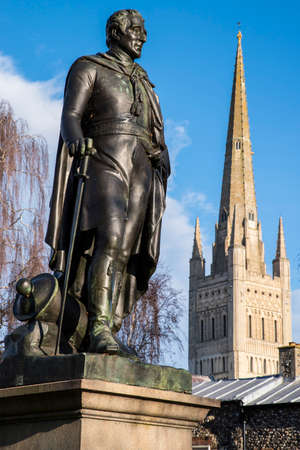 A statue of the Duke of Wellington with the beautiful Norwich Cathedral in the background, in the historic city of Norwich, UK.
