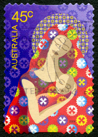 AUSTRALIA - CIRCA 2004: A used postage stamp from Australia, depicting a festive illustration of Mary with baby Jesus, celebrating the Christmas season, circa 2004.