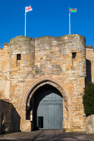 The English and Lincolnshire flags flying proudly above the East Gate of Lincoln Castle in the UK.