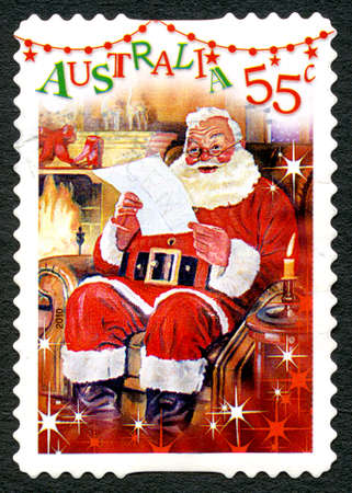 AUSTRALIA - CIRCA 2010: A used postage stamp from Australia, depicting a festive scene of Santa Claus reading a letter by the fireplace, circa 2010. Editorial