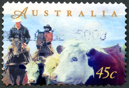 philately: AUSTRALIA - CIRCA 1998: A used postage stamp from Australia, depicting an illustration of farmers herding cattle on horseback, circa 1998.