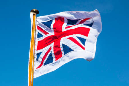 A shot of the Union Flag or Union Jack flying over a clear blue sky.  With the surrounding white border, the flag is called the Pilot Jack and is used on a boat when it is in harbour. Stock Photo