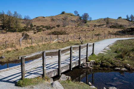 northwest: A footbridge connecting the circular path surrounding the beautiful Tarn Hows in the Lake District in Cumbria, UK.