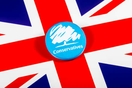 local council election: LONDON, UK - MAY 2ND 2017: A Conservative Party pin badge over the UK flag, on 2nd May 2017. Editorial