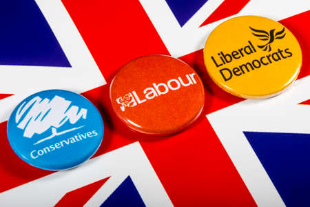 conservative: LONDON, UK - MAY 2ND 2017: Conservatives, Labour and Liberal Democrat pin badges over the UK flag, symbolizing the political battle for the General Election, on 2nd May 2017 Editorial