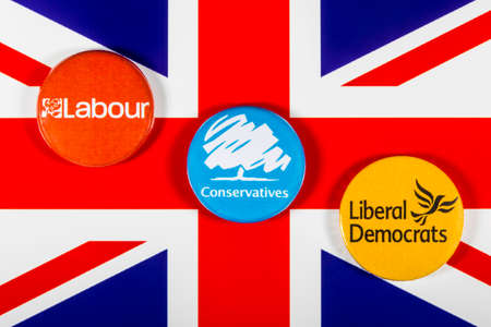 local council election: LONDON, UK - MAY 2ND 2017: Labour, Conservatives and Liberal Democrat pin badges over the UK flag, symbolizing the political battle for the General Election, on 2nd May 2017. Editorial