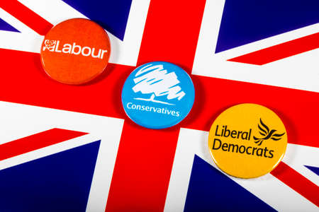 LONDON, UK - MAY 2ND 2017: Labour, Conservatives and Liberal Democrat pin badges over the UK flag, symbolizing the political battle for the General Election, on 2nd May 2017. Editorial