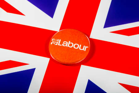 local council election: LONDON, UK - MAY 2ND 2017: A Labour Party pin badge over the UK flag, on 2nd May 2017.