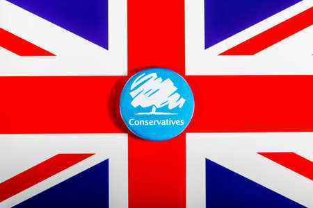 LONDON, UK - MAY 2ND 2017: A Conservative Party pin badge over the UK flag, on 2nd May 2017. Editorial