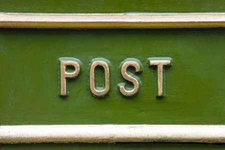 Close-up of the word POST on a traditional Victorian post box in the UK.