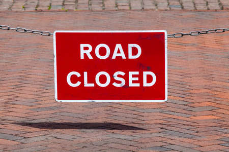 A Road Closed Sign hanging from a chain. Imagens