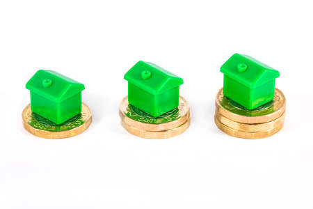 first time buyer: Green Houses sitting on top of stacks of coins, over a white background.