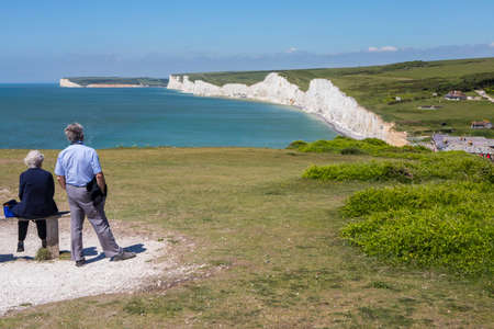 EAST SUSSEX, UK - MAY 25TH 2017: A couple take in the beautiful view from Birling Gap of the Seven Sisters white chalk cliffs in East Sussex, UK, on 25th May 2017. Editorial