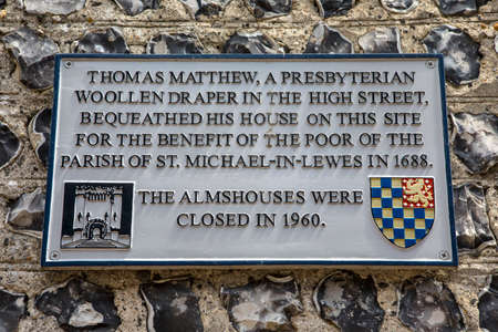 almshouse: LEWES, UK - MAY 31ST 2017: A plaque noting the history of a house on the historic Keere Street in Lewes, East Sussex, UK, on 31st May 2017.