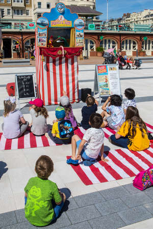 brighton: BRIGHTON, UK - MAY 31ST 2017: A group of children watching a traditional Punch and Judy puppet show on the seafront in Brighton, UK, on 31st May 2017.