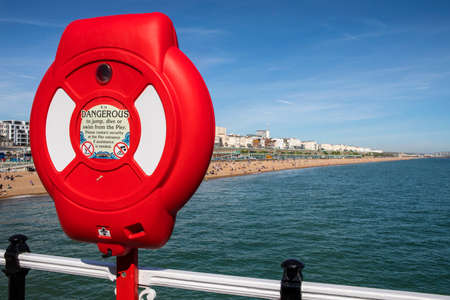 brighton: BRIGHTON, UK - MAY 31ST 2017: A Life-Saving Ring and the view from the historic Brighton Pier in Brighton, East Sussex, on 31st May 2017.