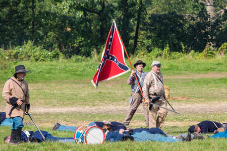KENT, UK - AUGUST 28TH 2017: Actors posing as Confederate soldiers from the American Civil War standing over fallen Union soldiers, at the Military Odyssey Re-enactment event in Detling, Kent, on 28th August 2017.