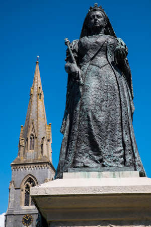 WEYMOUTH, UK - AUGUST 15TH 2017: A statue of Queen Victoria, located on Weymouth seafront in Dorset, UK, on 15th August 2017. The spire of St Johns Church is in the background.